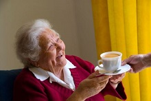 Happy elderly lady receives a cup of tea from carer  nurse companion in her light airy sitting room